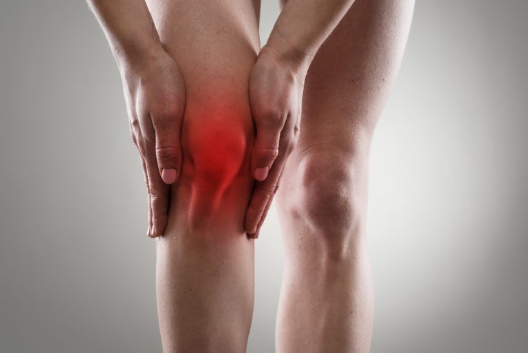 women holding sore knee